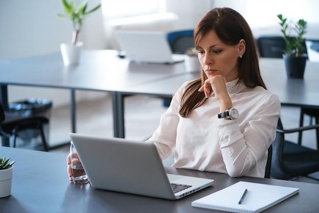 Jonge, aantrekkelijke en zekere bedrijfsvrouw die in bureau werkt