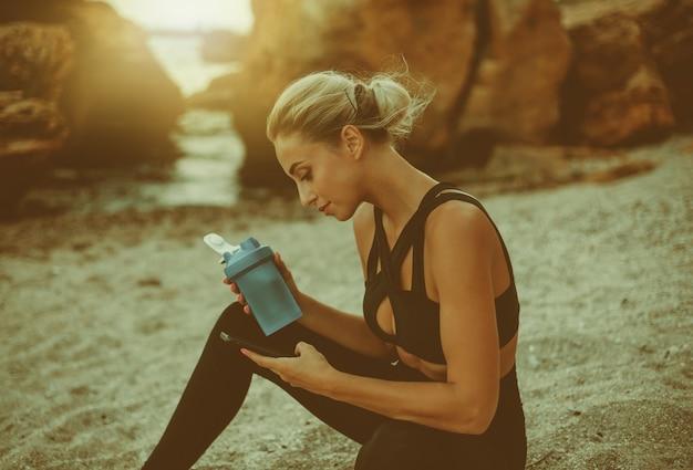 Jonge aantrekkelijke fit vrouw in sportkleding rust na de training zittend op het zand op het wilde strand. sportvrouw gebruikt een smartphone en drinkt water uit een fles