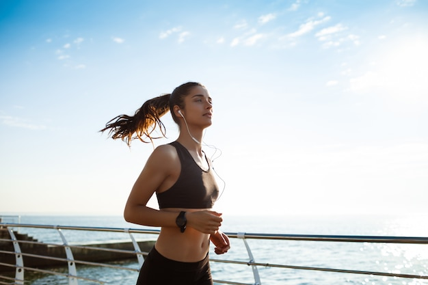 Jonge aantrekkelijke fitness meisje joggen door de zee