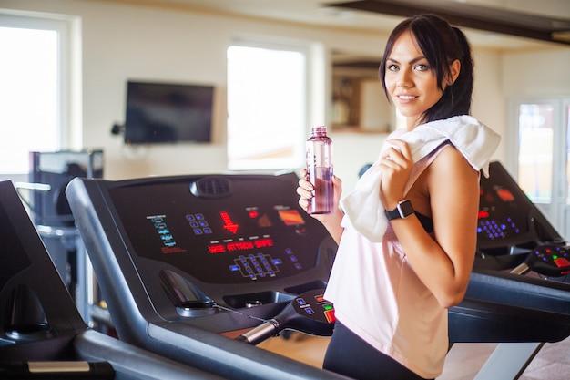 Jonge aantrekkelijke fitness vrouw die op tredmolen loopt, die in witte sportkleding, gezonde sportieve vrouw draagt die cardiooefening op tredmolen doet