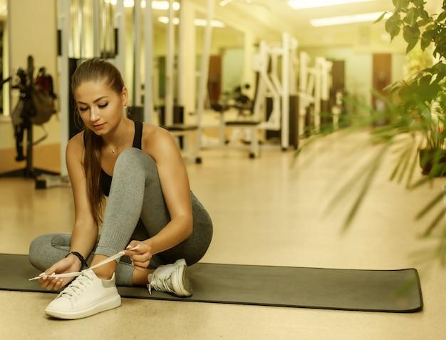 Jonge aantrekkelijke fitte vrouw die veters van sportschoenen bindt terwijl ze op een mat in de sportschool zit