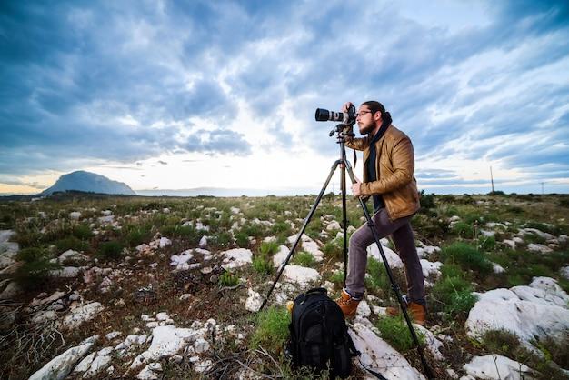Jonge aantrekkelijke fotograaf die foto's met camera op driepoot maken bij zonsondergang