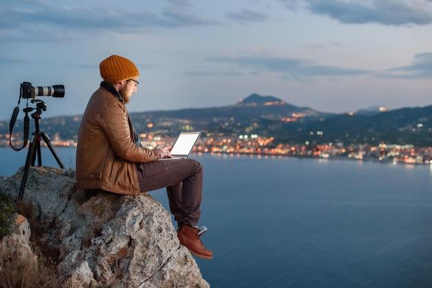 Jonge aantrekkelijke fotograaf zittend op rock en bezig met laptop met uitzicht op zee en bergen