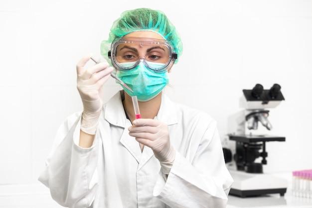 Jonge aantrekkelijke geconcentreerde vrouwelijke wetenschapper in beschermende oogglazen