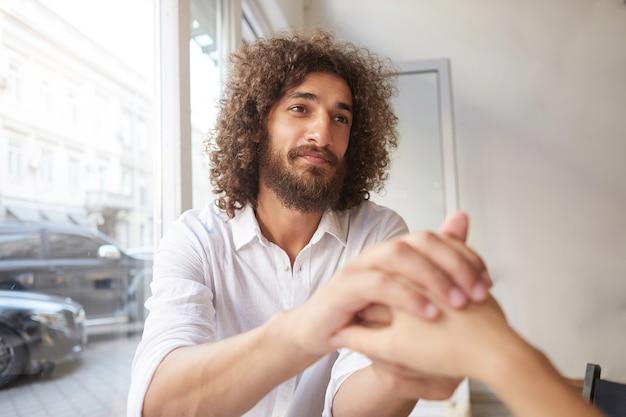 Jonge aantrekkelijke gekrulde man met baard en bruine vriendelijke ogen zit bij het raam, houdt vrouwelijke hand vast en kijkt haar duur aan, draagt een wit overhemd