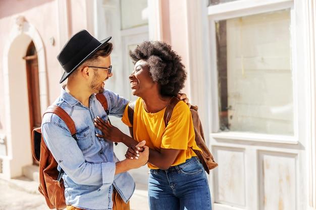 Jonge aantrekkelijke gelukkige multiraciale paar staande buiten op een mooie zonnige dag flirten.