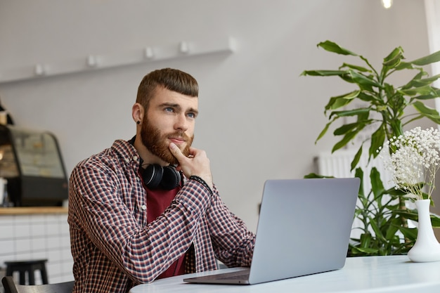 Jonge aantrekkelijke gember bebaarde man zit aan een tafel in een café en werkt op een laptop, gekleed in eenvoudige kleding, bedachtzaam wegkijkend, in een poging een oplossing te bedenken.
