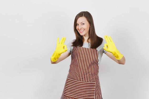 Jonge aantrekkelijke glimlachende donkerbruine huisvrouw in gestreepte schort, gele geïsoleerde handschoenen. mooie huishoudstervrouw die ok gebaar toont