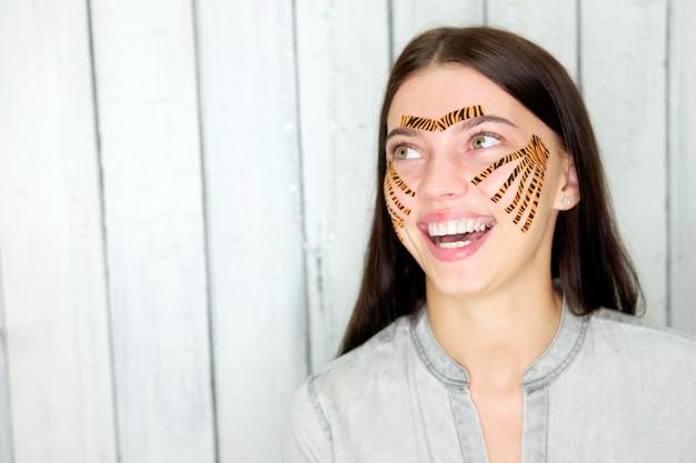 Jonge aantrekkelijke glimlachende donkerbruine vrouw met tijger gekleurde banden na het vastbinden gezichtsprocedure in schoonheidssalon