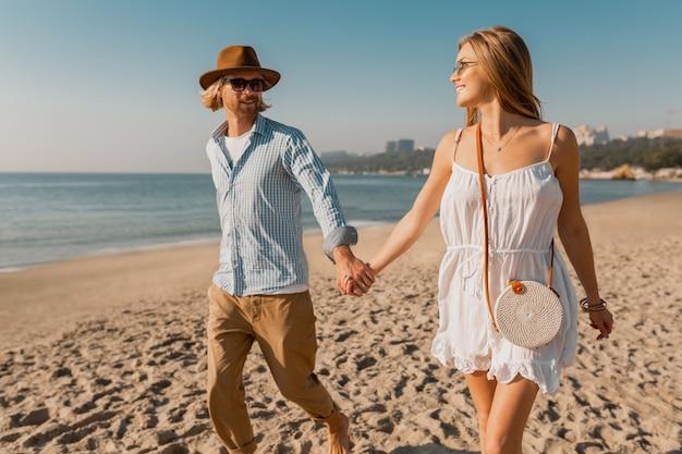 Jonge aantrekkelijke glimlachende gelukkig man in hoed en blonde vrouw in witte jurk die samen op strand loopt