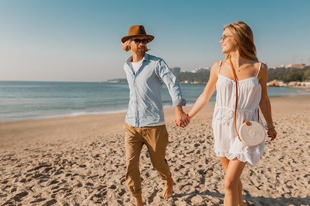 Jonge aantrekkelijke glimlachende gelukkige man in hoed en blonde vrouw in witte kleding die samen op strand lopen