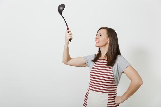 Jonge aantrekkelijke glimlachende kaukasische huisvrouw in gestreepte schort geïsoleerd. mooie huishoudster vrouw met zwarte keuken soeplepel