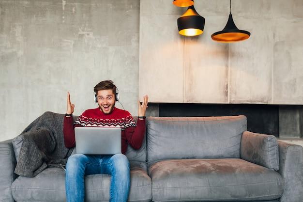 Jonge aantrekkelijke glimlachende man zittend op de bank thuis in de winter met verbaasde gezichtsuitdrukking, rode gebreide trui dragen, bezig met laptop, freelancer, emotioneel, schreeuwen, luisteren naar koptelefoon