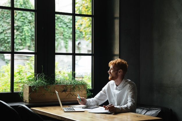 Jonge aantrekkelijke glimlachende roodharige gebaarde bedrijfsmens die venster bekijken terwijl het zitten op het werk