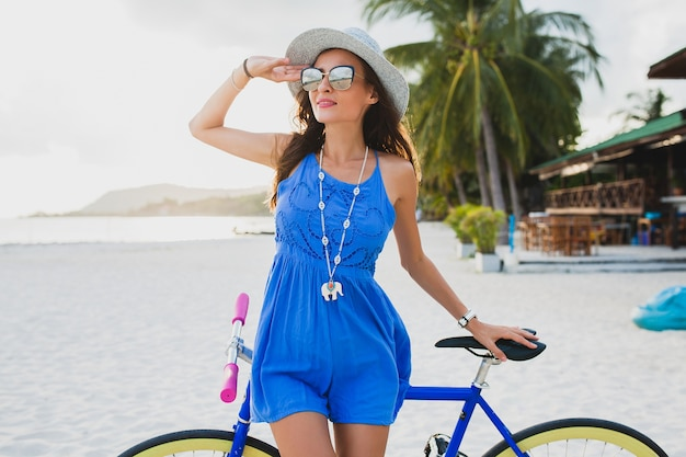 Jonge aantrekkelijke glimlachende vrouw die in blauwe kleding op tropisch strand met fiets loopt die hoed en zonnebril draagt