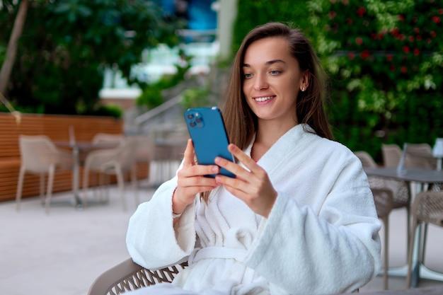 Jonge aantrekkelijke glimlachende vrouw die witte badjas draagt die smartphone gebruikt voor het bekijken van video en online browsen terwijl u ontspant in het kuuroord