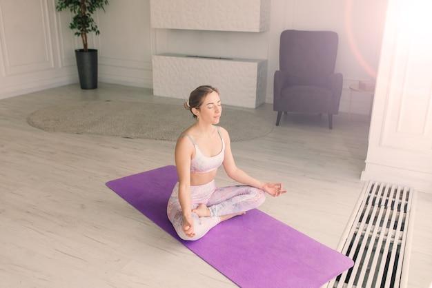 Jonge aantrekkelijke glimlachende vrouw die yoga beoefent, traint, sportkleding draagt, beha, thuistraining