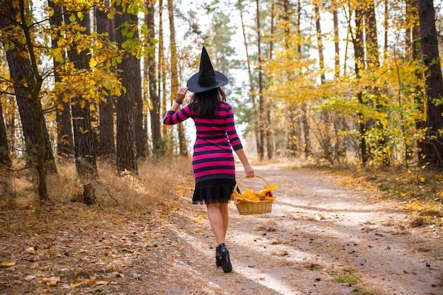 Jonge aantrekkelijke heks loopt in het herfst oranje foresthelloween concept
