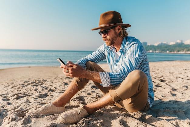 Jonge aantrekkelijke hipster man zittend op het strand aan zee op zomervakantie