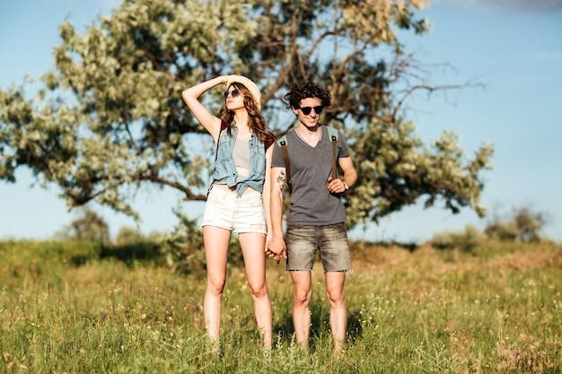 Jonge aantrekkelijke hipster paar staande tegen bomen op de achtergrond en hand in hand