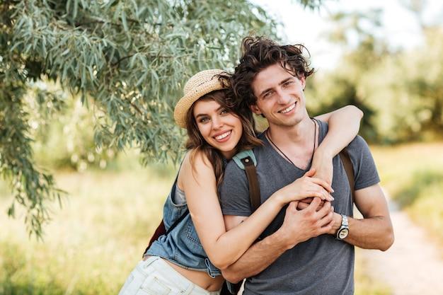 Jonge aantrekkelijke hipster paar staande tegen bomen op de achtergrond en knuffelen