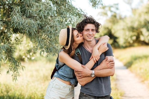 Jonge aantrekkelijke hipster paar staande tegen bomen op de achtergrond kussen en knuffelen