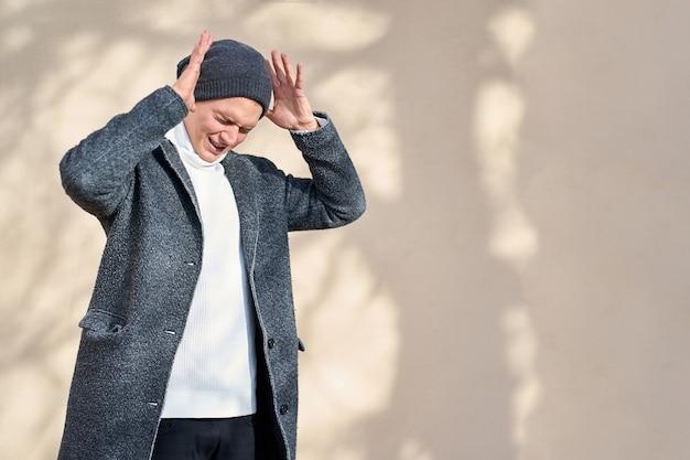 Jonge aantrekkelijke hipster trendy man met gesloten ogen, gekleed in een grijze jas, witte trui en zwarte spijkerbroek hand in hand in de buurt van hoofd en schreeuwen.