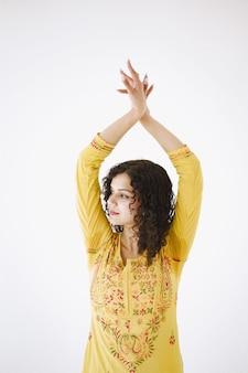 Jonge aantrekkelijke indiase vrouw in traditionele kleding. vrouw dansen tegen een witte achtergrond.