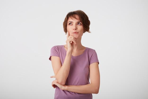 Jonge aantrekkelijke jonge kortharige vrouw in blanco t-shirt kijkt opzij, denkend. staat op een witte achtergrond.