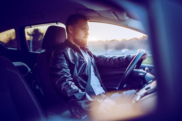Jonge aantrekkelijke kaukasische bebaarde blonde man in leren jas zijn nieuwe dure moderne auto rijden.