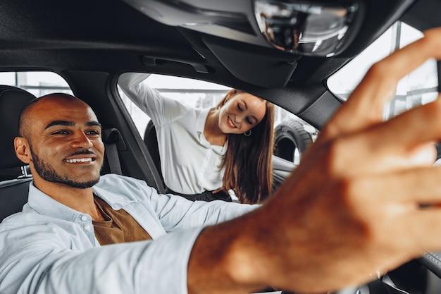 Jonge aantrekkelijke kaukasische vrouwenverkoper in autoshowroom die een auto toont aan haar mannelijke afrikaanse amerikaanse cliënt