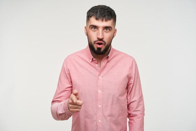 Jonge aantrekkelijke kortharige bebaarde man met open ogen die verbaasd kijkt en zijn wijsvinger opheft, vrijetijdskleding draagt terwijl hij over een witte muur staat