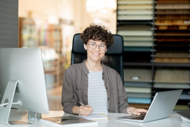Jonge aantrekkelijke krullende ontwerper die aantekeningen in kladblok maakt terwijl u achter laptop bij bureau zit