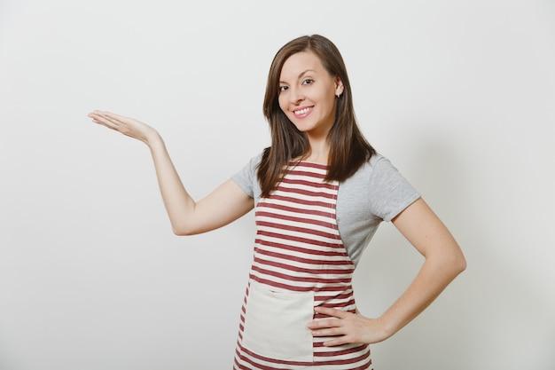 Jonge aantrekkelijke lachende brunette kaukasische huisvrouw in gestreepte schort geïsoleerd. mooie huishoudster vrouw wijzende hand opzij