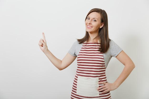 Jonge aantrekkelijke lachende brunette kaukasische huisvrouw in gestreepte schort geïsoleerd. mooie huishoudster vrouw wijzende wijsvinger omhoog