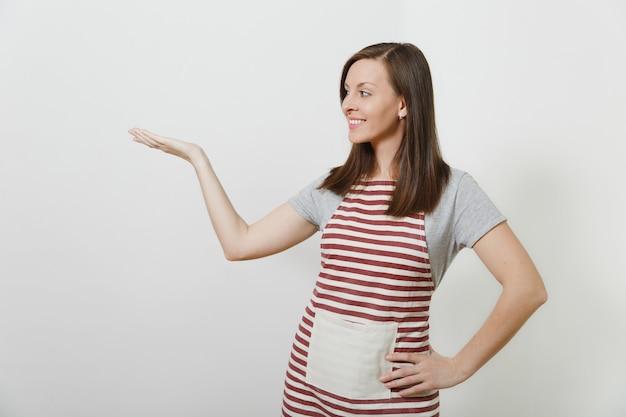 Jonge aantrekkelijke lachende brunette kaukasische huisvrouw in gestreepte schort geïsoleerd. mooie huishoudstervrouw die de hand opzij wijst en opzij kijkt
