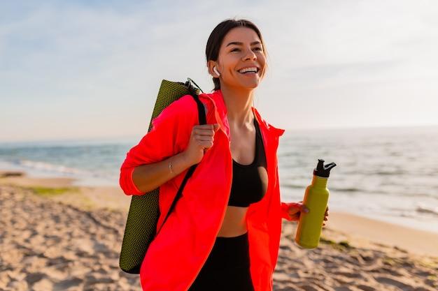 Jonge aantrekkelijke lachende vrouw doet sport in de ochtend zonsopgang op zee strand yoga mat en fles water te houden, gezonde levensstijl, luisteren naar muziek op oortelefoons, roze windjack dragen