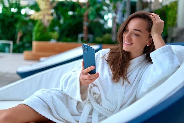 Jonge aantrekkelijke lachende vrouw draagt witte badjas met smartphone voor het bekijken van video en online browsen terwijl liggend op een ligstoel tijdens het ontspannen in het kuuroord