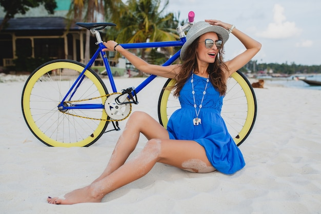 Jonge aantrekkelijke lachende vrouw in blauwe jurk zittend op zand op tropisch strand met fiets hoed en zonnebril dragen