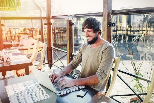 Jonge aantrekkelijke man aan het werk met laptop op terras