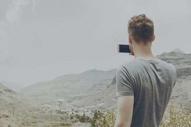 Jonge aantrekkelijke man die foto maakt van natuur landschap met zijn smartphone. toning.