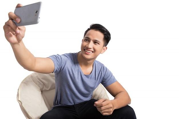 Jonge aantrekkelijke man die zelf foto's maakt (selfie) met s