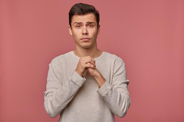 Jonge aantrekkelijke man draagt een blanco lange mouw, doet een wens, hoopt op veel geluk bij examens en gekruiste handpalmen, vraagt om hem geen slecht cijfer te geven, staat op een roze achtergrond.
