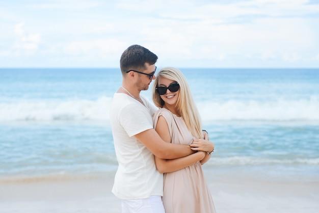 Jonge aantrekkelijke man en vrouw verliefd lopen en knuffelen op wit zand en azuurblauwe zee. reizen, huwelijksreis