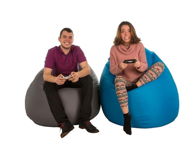 Jonge aantrekkelijke man en vrouw zittend op blauwe en grijze zitzak stoelen voor woonkamer of andere kamer en spelen van videogames geïsoleerd op wit