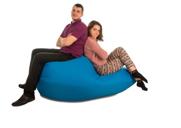 Jonge aantrekkelijke man en vrouwenzitting op blauwe zitzakbank voor woonkamer of andere ruimte die op wit wordt geïsoleerd