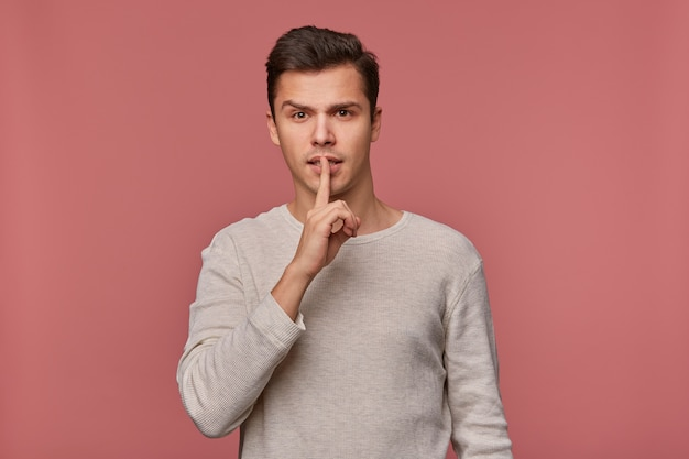 Jonge aantrekkelijke man in blanco lange mouw, staat op een roze achtergrond en toont een stil gebaar, blijf alsjeblieft kalm en stil .;
