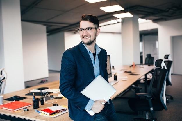 Jonge aantrekkelijke man in glaasje met baard staat in de buurt van de werkplek op kantoor. hij draagt een blauw shirt, een donkere jas, een laptop in de hand. hij glimlacht opzij.