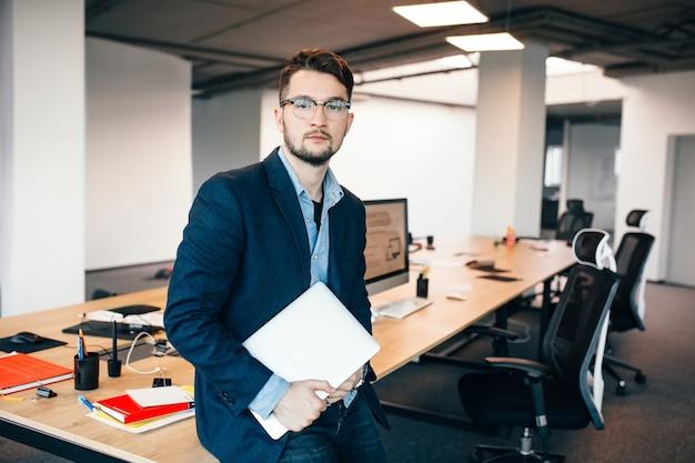 Jonge aantrekkelijke man in glaasje staat in de buurt van de werkplek op kantoor. hij draagt een blauw shirt, een donkere jas, een laptop in de hand. hij kijkt naar de camera.