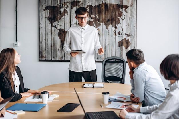 Jonge aantrekkelijke man in glazen met een tablet in zijn handen presenteert zijn project tijdens een vergadering
